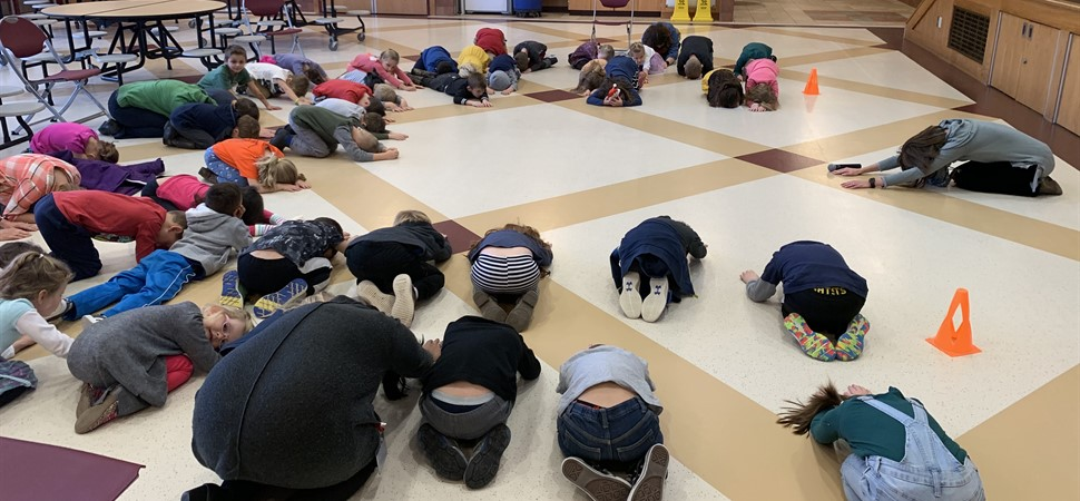 Wellness moment and yoga at weekly kindergarten assembly